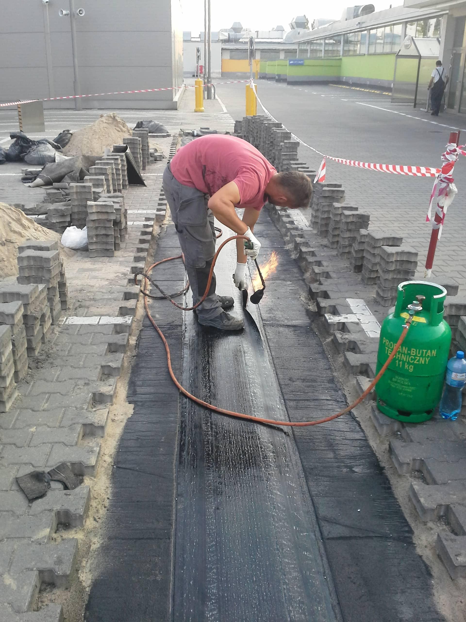 Wykonanie izolacji przeciwwodnej dylatacji parkingu z papy termozgrzewalnej.
